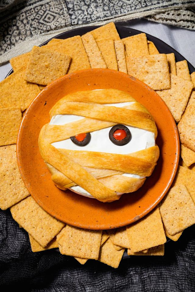 """<p>Thanks to puff pastry, your basic baked brie becomes a totally spooky Halloween appetizer.</p><p>Get the recipe from <a rel=""""nofollow"""" href=""""http://www.delish.com/holiday-recipes/halloween/recipes/a49347/mummy-brie-recipe/"""">Delish</a>.</p>"""