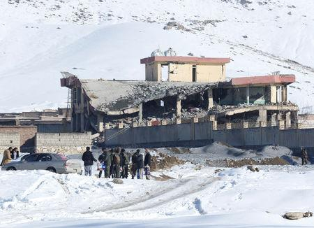 Afghan men stand in front of a collapsed building of a military base after a car bomb attack in Maidan Wardak