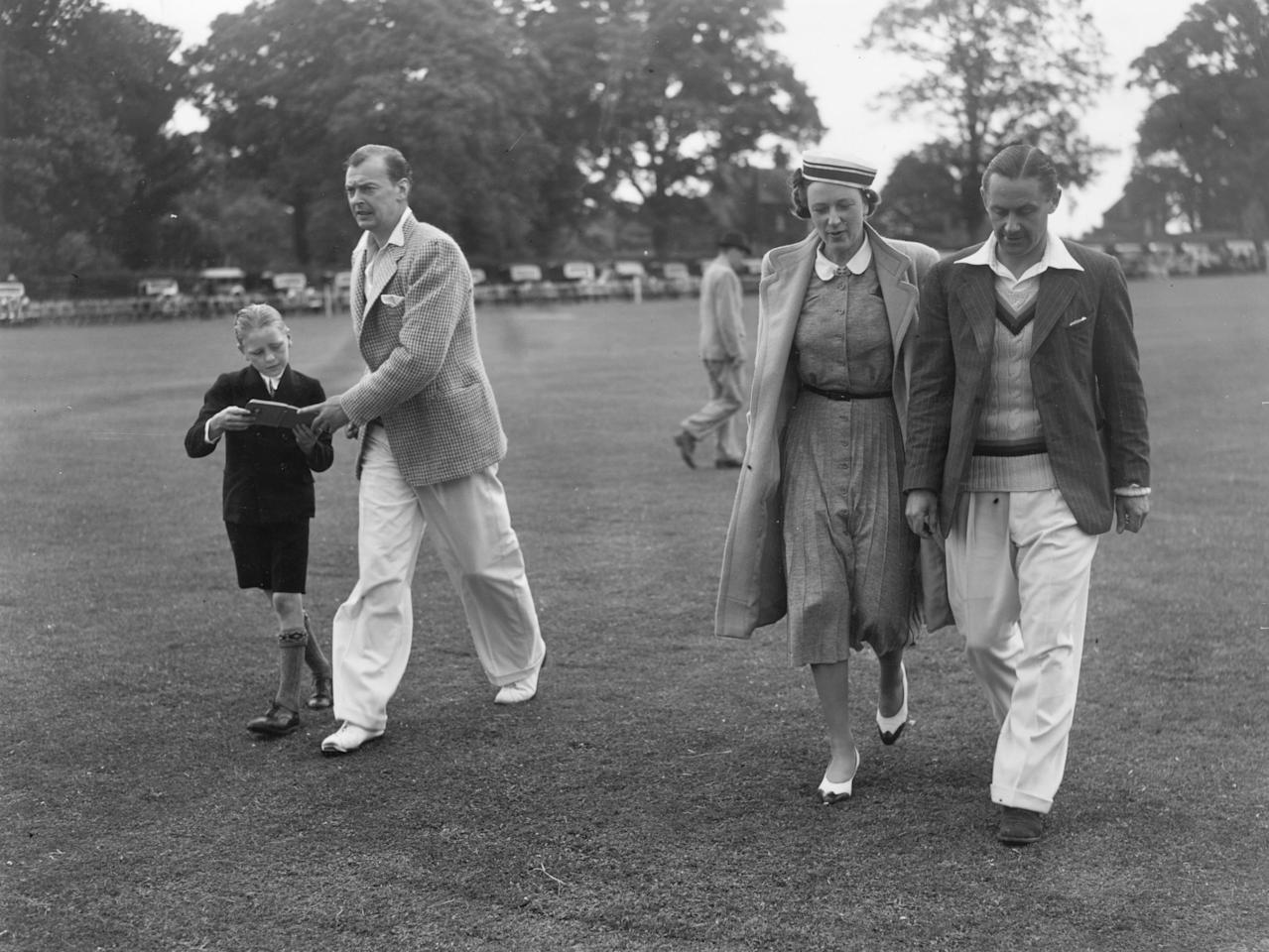 19th July 1939:  Ian Peebles (1908- 1980) cricket (bowler) player for Middlesex and England (1927 - 1931) returning an autograph book to a boy fan. Mrs A P F Chapman and George 'Gubby'Allen (1902 - 1989)  cricket player for Middlesex and England (1930 - 1948), Knighted in 1986.  (Photo by J. A. Hampton/Topical Press Agency/Getty Images)