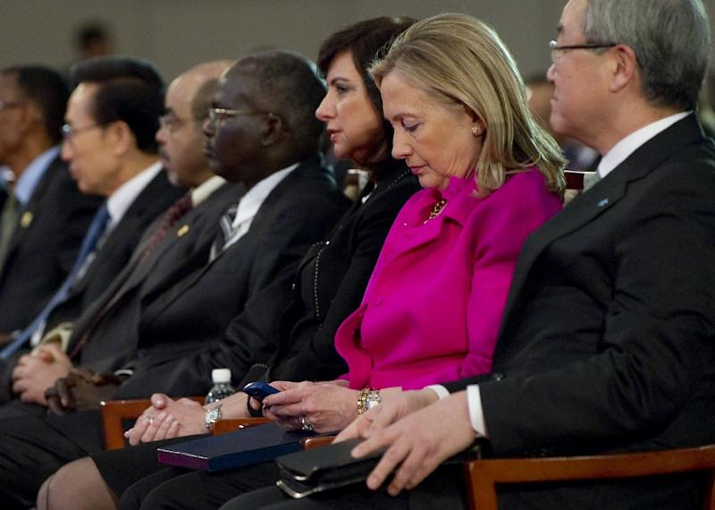 Former US Secretary of State Hillary Clinton (2nd R) checks her Blackberry phone as she attended an event in Busan, Korea, November 30, 2011