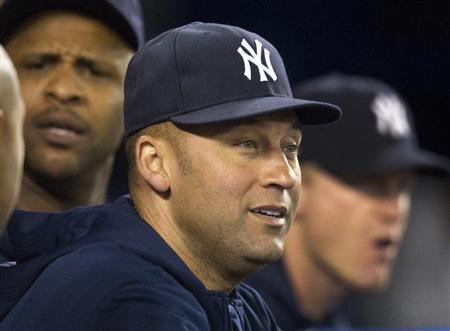 New York Yankees Jeter watches play from the dugout during their American League MLB baseball game against Toronto Blue Jays in Toronto