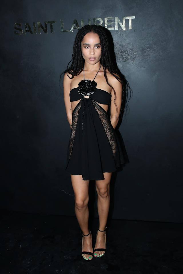 Zoe hit the red carpet at Paris Fashion week in this black halter minidress with a statement flower at the neckline.