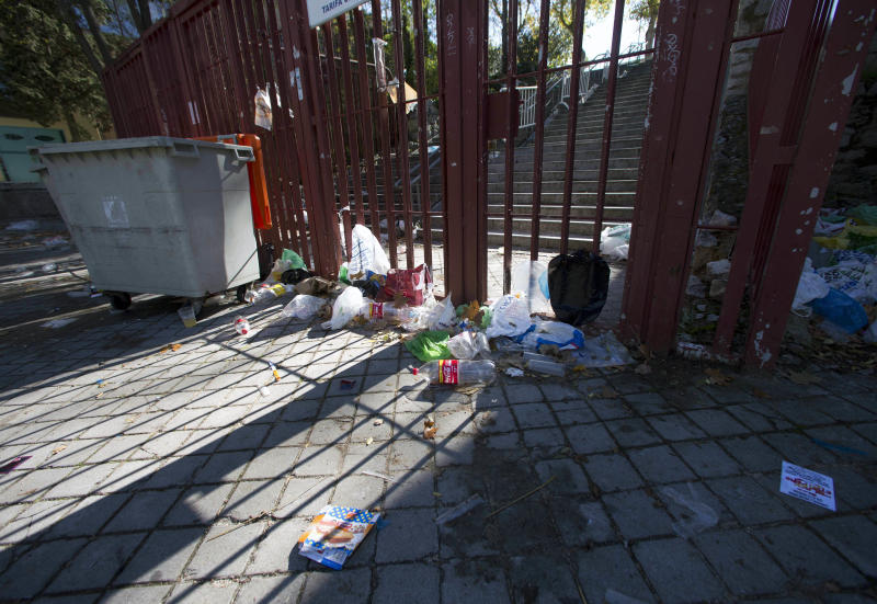 Empty bottles and other debris lie outside the closed gates of the Madrid Arena venue in Madrid, Thursday Nov. 1, 2012.  Three women have been killed and two injured in a stampede during a large Halloween Night party at the venue. Emergency services spokesman Fernando Prado said the women, aged between 18-25 years old, suffered trauma injuries and heart failure compatible with having been crushed during a stampede after a flare was reportedly set off within Madrid Arena in the west of the city, where thousands of people were partying early Thursday. Halloween has recently become a popular festivity in Spain coinciding with the traditional feast of All Saints. (AP Photo/Paul White)