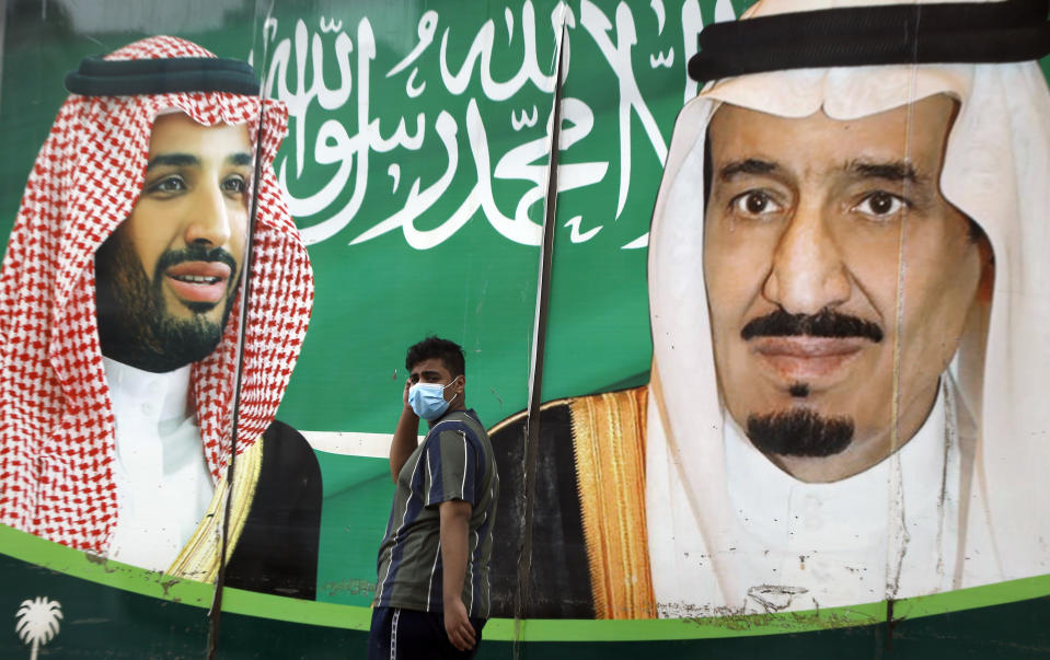 FILE PHOTO: A man wearing a face mask to help curb the spread of the coronavirus walks past a banner showing Saudi King Salman, right, and his son Crown Prince Mohammed bin Salman, outside a mall in Jiddah, Saudi Arabia, Wednesday, Dec. 16, 2020. (AP Photo/Amr Nabil)