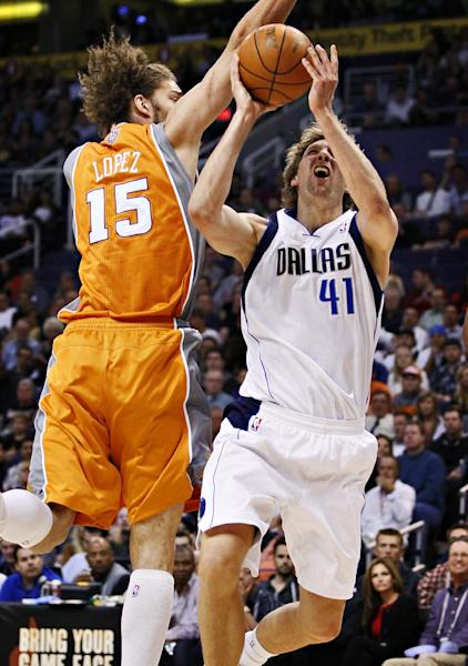 Dallas Mavericks' Dirk Nowitzki (41) goes up against Phoenix Suns' Robin Lopez (15) during the first half of an NBA basketball game, Thursday, March 8, 2012, in Phoenix. (AP Photo/Matt York)