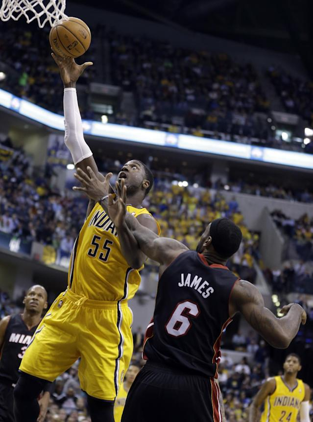 Indiana Pacers center Roy Hibbert (55) gets a bucket over Miami Heat forward LeBron James in the second half of an NBA basketball game in Indianapolis, Tuesday, Dec. 10, 2013. (AP Photo/Michael Conroy)
