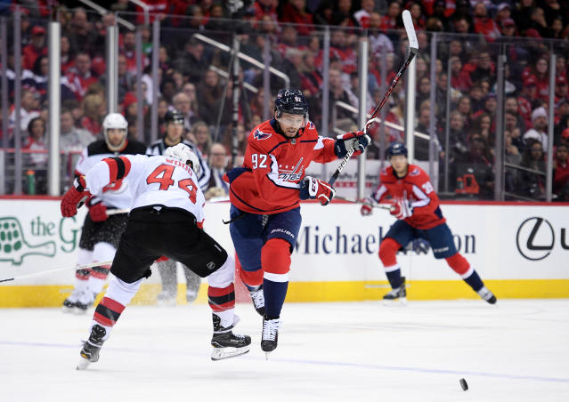 Washington Capitals center Evgeny Kuznetsov (92), of Russia, chases the puck next to New Jersey Devils left wing Miles Wood (44) during the second period of an NHL hockey game Saturday, April 7, 2018, in Washington. (AP Photo/Nick Wass)