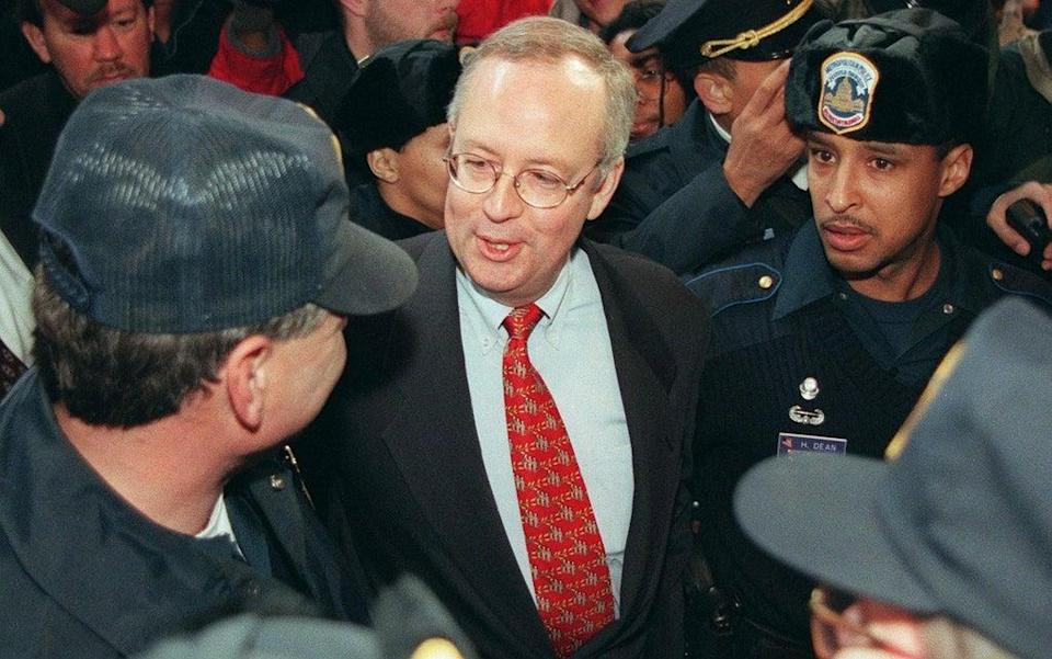 Kenneth Starr, independent counsel, speaks to a Washington, DC police officer as he is escorted away after speaking at a press conference on 22 January 1998 (LUKE FRAZZA/AFP via Getty Images)