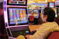 A gambler wears a mask while playing a slot machine at the Hard Rock casino in Atlantic City, N.J., on July 2, 2020, the day it reopened after being closed for just over three months due to the coronavirus outbreak. New Jersey's casinos and horse tracks won $2.88 billion in 2020, a decrease of nearly 17% from 2019, according to figures released Wednesday, Jan. 13, 2021, by the New Jersey Division of Gaming Enforcement. (AP Photo/Wayne Parry)