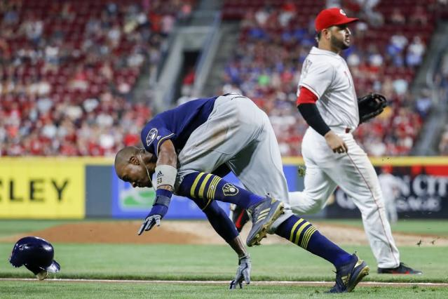 Milwaukee Brewers' runner Keon Broxton stumbles and even scores during wild rundown in win against Reds. (AP)