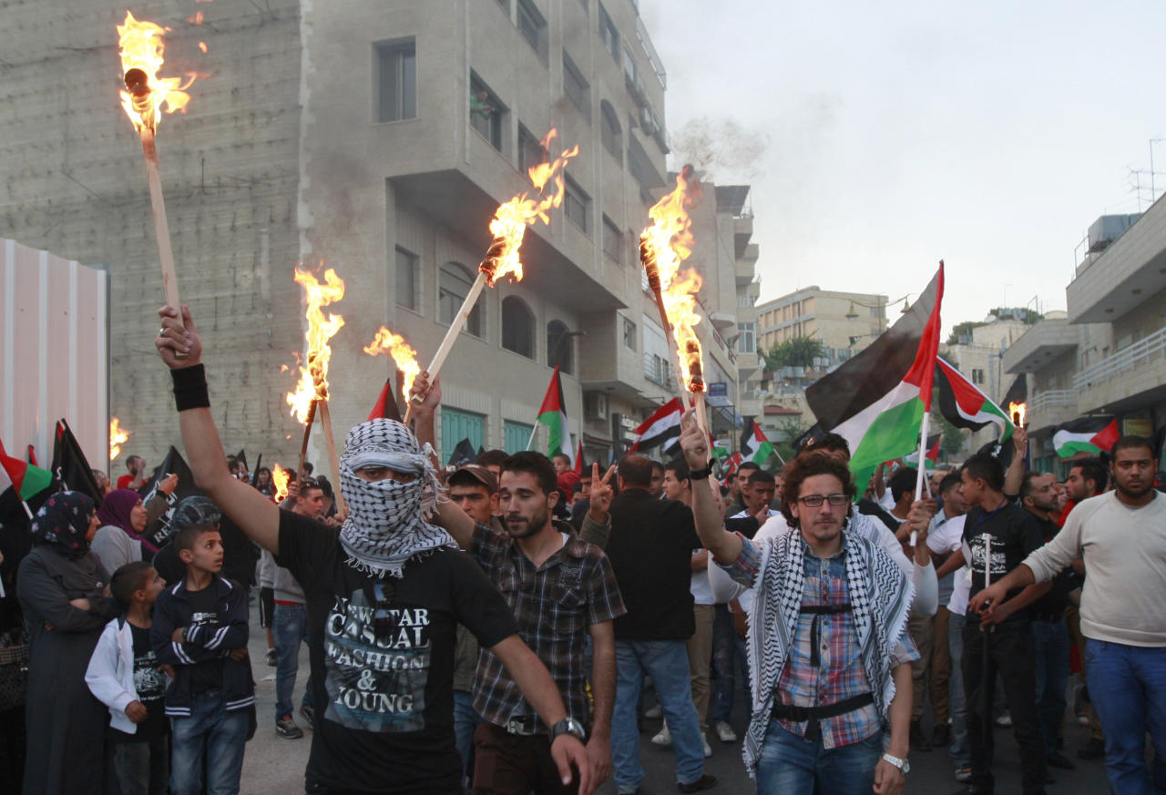 "People hold torches as Palestinians hold a rally to commemorate the 1948 creation of the Israeli state, known in Arabic as ""Nakba Day,"" or ""Day of the Catastrophe"" in the West Bank town of Bethlehem, Tuesday, May 14, 2013. (AP Photo/Majdi Mohammed)"