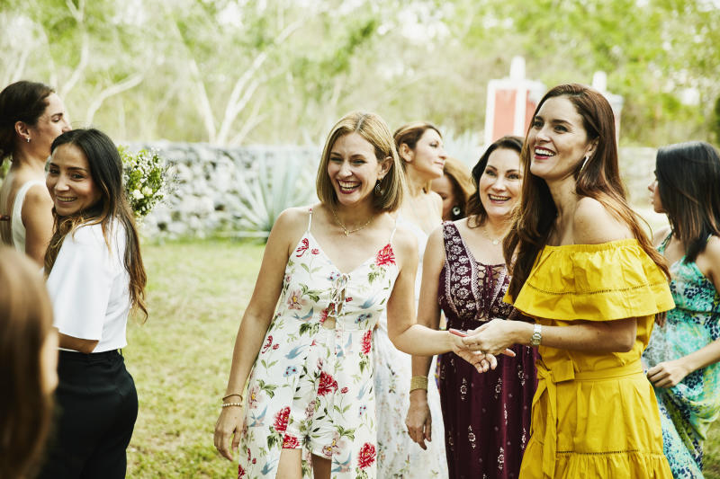 Laughing female friends in discussion during outdoor wedding reception