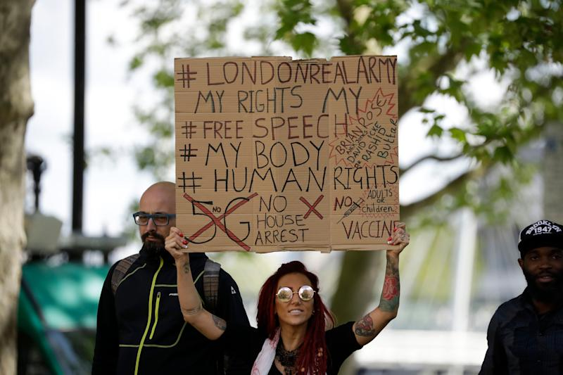 A woman holds up a placard at a coronavirus anti-lockdown, anti-vaccine, anti-5G and pro-freedom protest in London. (Photo: ASSOCIATED PRESS)