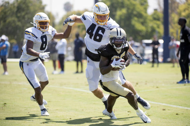 Los Angeles Chargers wide receiver Malachi Dupre (8) and tight end Matt Sokol (46) chase New Orleans Saints cornerback Ken Crawley after Crawley intercepted a pass intended for Dupre during a joint NFL football practice in Costa Mesa, Calif., Thursday, Aug. 15, 2019. (AP Photo/Kyusung Gong)
