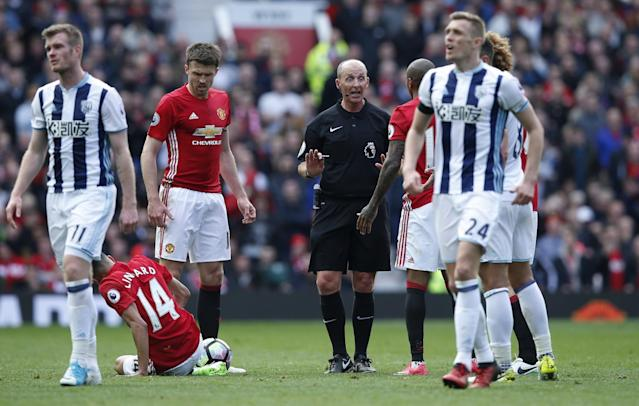 <p>Referee Mike Dean speaks to Manchester United's Ashley Young as Jesse Lingard is down </p>