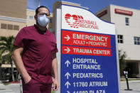 Rublas Ruiz poses for a photograph outside of Kendall Regional Medical Hospital where he works as a nurse in the hospital's intensive care unit, Tuesday, Aug. 11, 2020, in Miami. While other nurses rotate in and out of the COVID-19 ICU unit to limit their exposure to the deadly virus, Ruiz has asked to stay permanently. (AP Photo/Lynne Sladky)