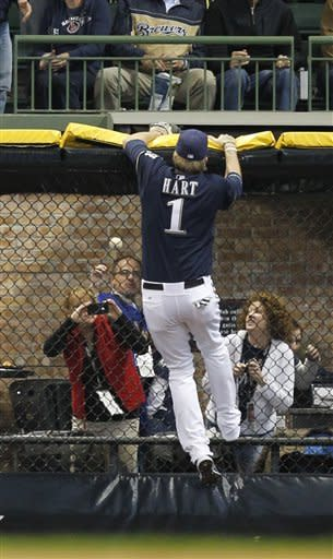 Milwaukee Brewers' Corey Hart leaps at the wall but cannot come up with a home run hit by Houston Astros' Jed Lowrie during the first inning of a baseball game Monday, April 23, 2012, in Milwaukee. (AP Photo/Jeffrey Phelps)