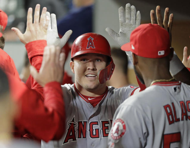Los Angeles Angels' Mike Trout is greeted in the dugout after he hit a two-run home run during the seventh inning against the Seattle Mariners in a baseball game Tuesday, June 12, 2018, in Seattle. It was Trout's second home run of the game. (AP Photo/Ted S. Warren)