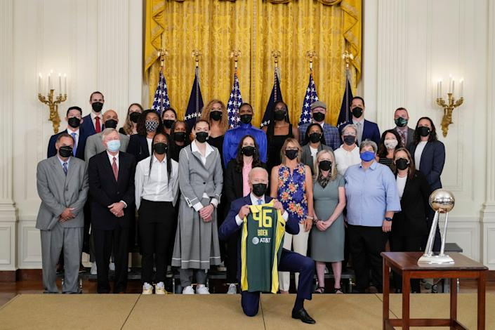 President Joe Biden holds a jersey as he poses for a photo with the 2020 WNBA champions Seattle Storm in the East Room of the White House on August 23, 2021 in Washington, DC. The Storm defeated the Last Vegas Aces in the 2020 WNBA Finals to win their 4th title as a franchise.