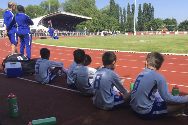 In this Saturday, May 5, 2018 photo, children wait to play in the Torcy Cup, in Torcy, east of Paris, France. The tournament is organized by US Torcy, the amateur club in the Paris suburb of Torcy where France midfielder Paul Pogba played when he was a teenager. Not all the money that will change hands after the World Cup, when clubs trade players who distinguish themselves on footballs biggest stage, will line the pockets of selling clubs, agents and the players themselves. A sliver of the wealth will also trickle down to footballs grassroots, to unpretentious, volunteer-run clubs where kids take first steps toward their dreams of making a career in the sport. (AP Photo/John Leicester)