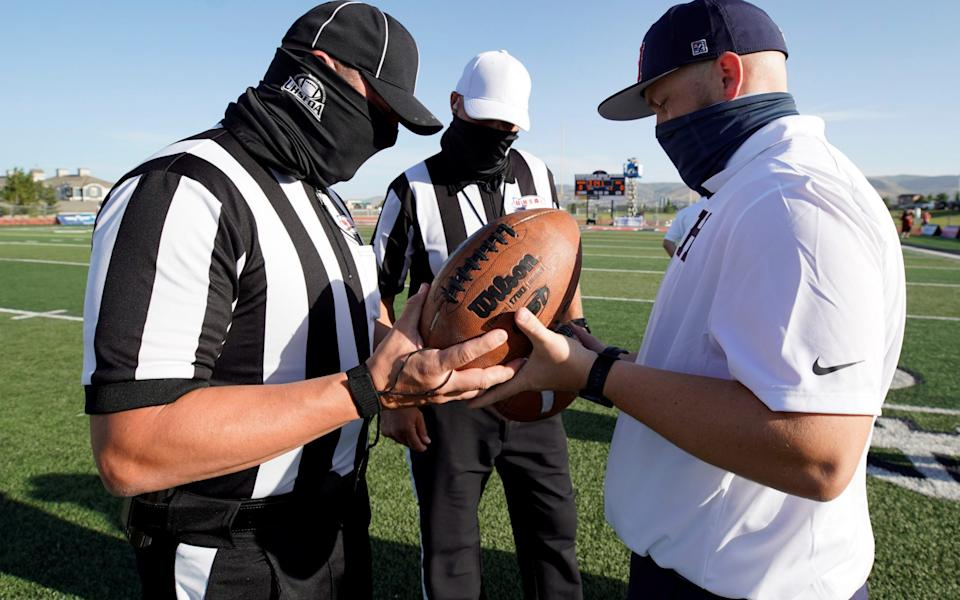 Masked officials check out the game balls before a game - REUTERS/GEORGE FREY