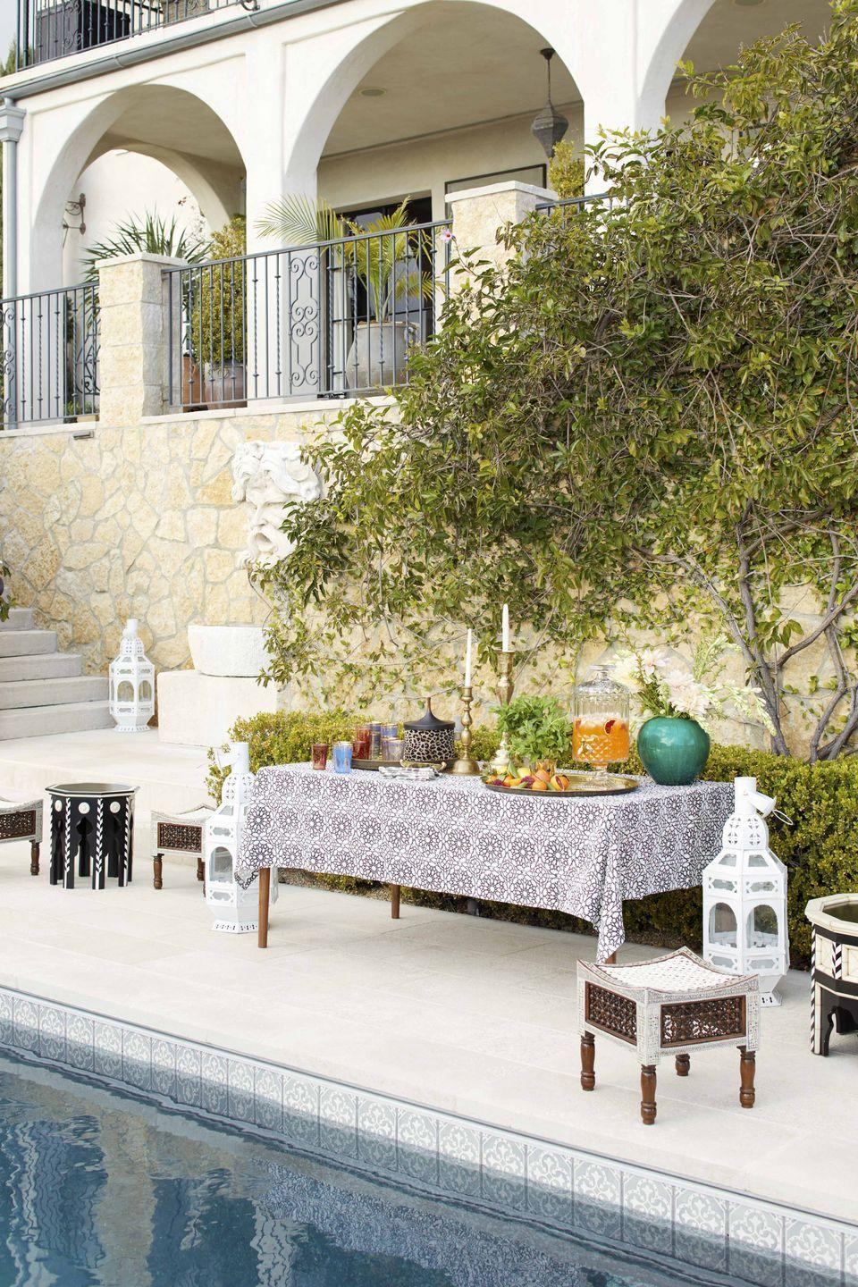 """<p>When designer Martyn Lawrence Bullard teamed up with friend and client Ellen Pompeo to host a <a href=""""https://www.veranda.com/luxury-lifestyle/a27105011/ellen-pompeo-martyn-lawrence-bullard-hollywood-entertaining/"""" rel=""""nofollow noopener"""" target=""""_blank"""" data-ylk=""""slk:Moroccan soiree"""" class=""""link rapid-noclick-resp"""">Moroccan soiree</a>, he twirled up a table for serving poolside cocktails with a tablecloth made from his fabric line. The tables are from <a href=""""https://martynlawrencebullard.com/products/mlb-furniture-atelier/"""" rel=""""nofollow noopener"""" target=""""_blank"""" data-ylk=""""slk:Martyn Lawrence Bullard Atelier & Furniture"""" class=""""link rapid-noclick-resp"""">Martyn Lawrence Bullard Atelier & Furniture</a>, and the Moroccan lanterns are from <a href=""""https://www.berbereworldimports.com/"""" rel=""""nofollow noopener"""" target=""""_blank"""" data-ylk=""""slk:Berbere World Imports"""" class=""""link rapid-noclick-resp"""">Berbere World Imports</a>.</p>"""