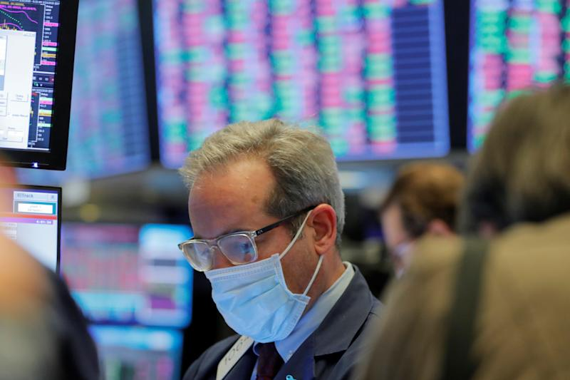 A trader wears a mask as he works on the floor of the New York Stock Exchange (NYSE) as the building prepares to close indefinitely due to the coronavirus disease (COVID-19) outbreak in New York, U.S., March 20, 2020. REUTERS/Lucas Jackson