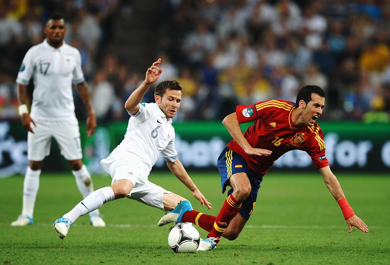 DONETSK, UKRAINE - JUNE 23: Yohan Cabaye of France tackles Sergio Busquets of Spain during the UEFA EURO 2012 quarter final match between Spain and France at Donbass Arena on June 23, 2012 in Donetsk, Ukraine.  (Photo by Laurence Griffiths/Getty Images)