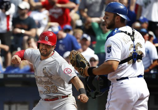 St. Louis Cardinals' Daniel Descalso (33) celebrates in front of Kansas City Royals catcher George Kottaras (26) after scoring a run during the sixth inning of a baseball game at Kauffman Stadium in Kansas City, Mo., Monday, May 27, 2013. (AP Photo/Orlin Wagner)