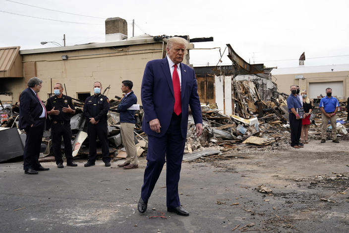 President Donald Trump tours an area on Tuesday damaged during demonstrations after a police officer shot Jacob Blake in Kenosha, Wis.
