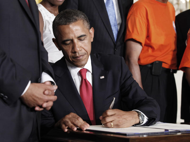 President Barack Obama signs the Surface Transportation Bill, HR 4348, during a ceremony in the East Room of the White House in Washington, Friday, July 6, 2012. The bill maintains jobs on transportation projects and prevents interest rate increases on new loans to millions of college students. (AP Photo/Pablo Martinez Monsivais)