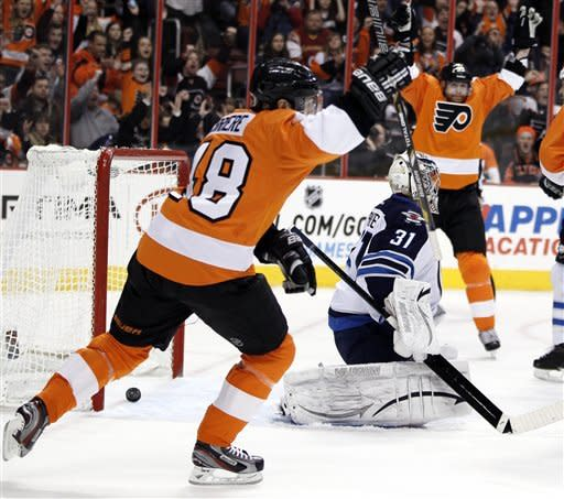 Philadelphia Flyers Danny Briere, left, and Jakub Voracek, rear, celebrate Claude Giroux's power-play goal past Winnipeg Jets Ondrej Pavelec, center, in the second period of an NHL hockey game, Saturday, Feb 23, 2013, in Philadelphia. (AP Photo/Tom Mihalek)