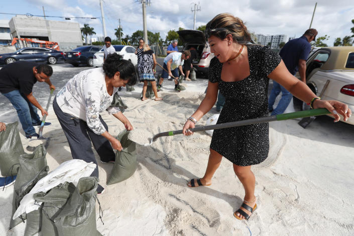 Georgia Bernard, right, and Ana Perez are among residents filling sandbags to take home in preparation for Hurricane Dorian, Friday, Aug. 30, 2019, in Hallandale Beach, Fla., as the town allowed residents to fill up sandbags until they ran out. All of Florida is under a state of emergency and authorities are urging residents to stockpile a week's worth of food and supplies as Hurricane Dorian gathers strength and aims to slam the state as soon as Monday as a Category 4 storm. (AP Photo/Wilfredo Lee)