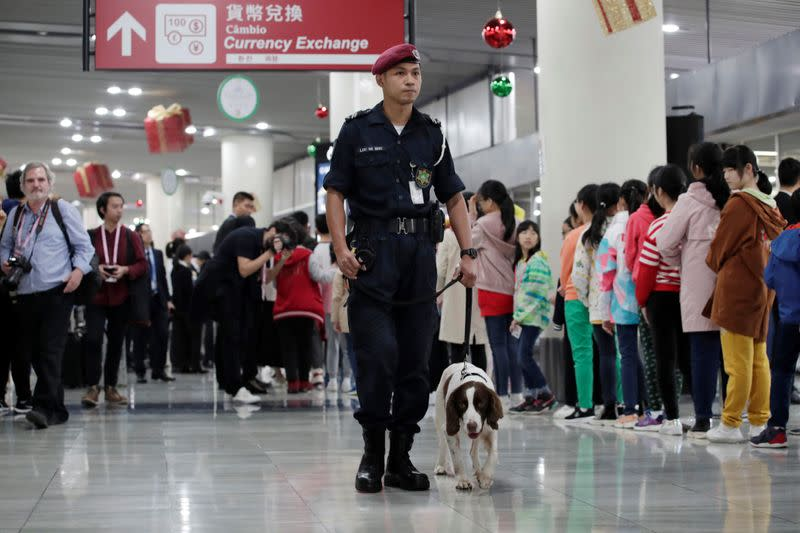 Security personnel walks with a sniffer dog before Chinese President Xi Jinping's arrival at Macau International Airport in Macau