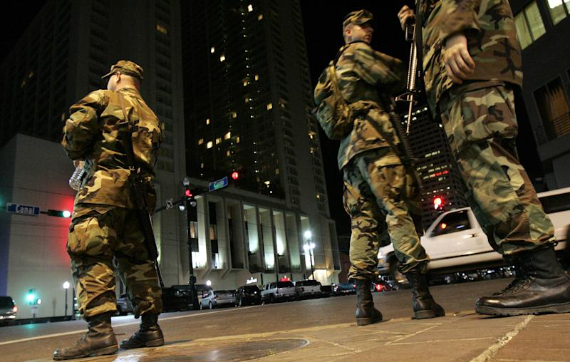 Soldiers with the Washington State National Guard pause while patrolling Canal Street in New Orleans, Monday, Oct. 3, 2005. Even though the French Quarter has re-opened for partying, a dusk to dawn curfew remains in effect for the city as it recovers from Hurricane Katrina. (AP Photo/LM Otero)