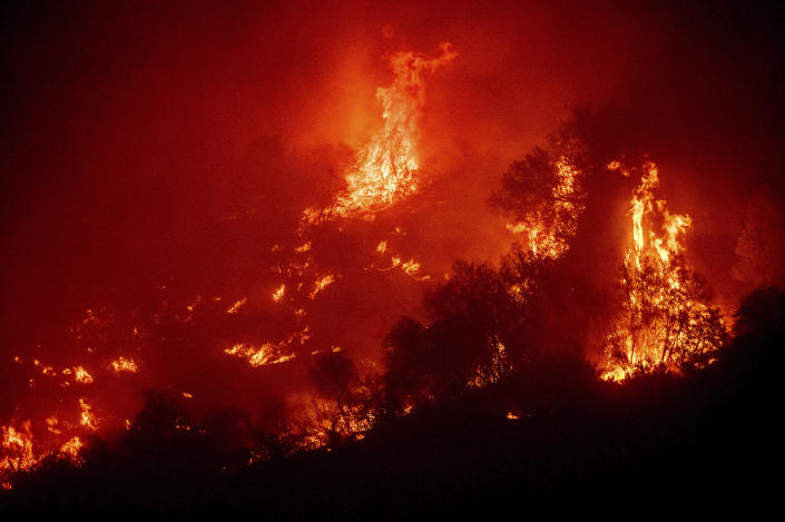 Flames from the KNP Complex Fire burn a hillside above the Kaweah River in Sequoia National Park, Calif., on Tuesday, Sept. 14, 2021. The blaze is burning near the Giant Forest, home to more than 2,000 giant sequoias. (AP Photo/Noah Berger)