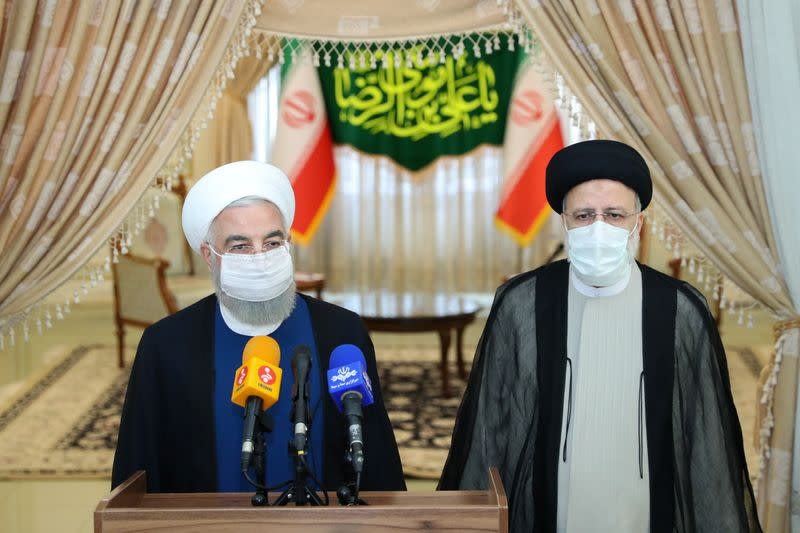 Iran's outgoing President Rouhani and Iran's President-elect Raisi speak to the media after their meeting, in Tehran