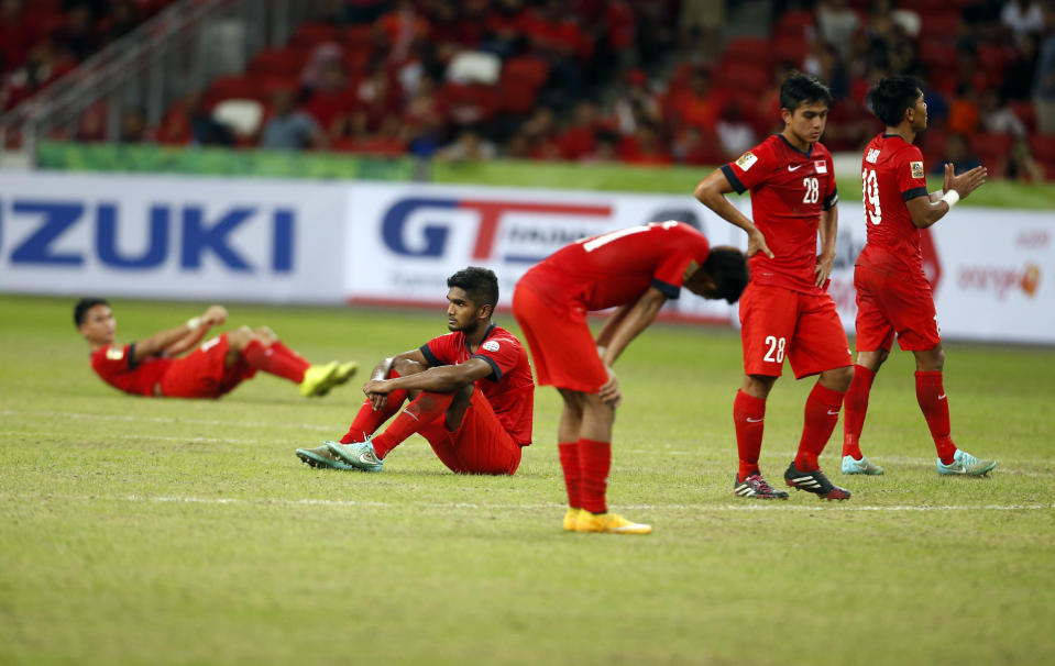 Singapore's players react after losing to Malaysia at the 2014 Suzuki Cup group stage.