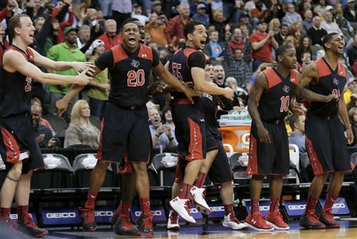 Texas Tech's bench celebrates after Dejan Kravic made the game-winning basket during the second half an NCAA college basketball game against West Virginia in the Big 12 men's tournament Wednesday, March 13, 2013, in Kansas City, Mo. Texas Tech won 71-69. (AP Photo/Charlie Riedel)