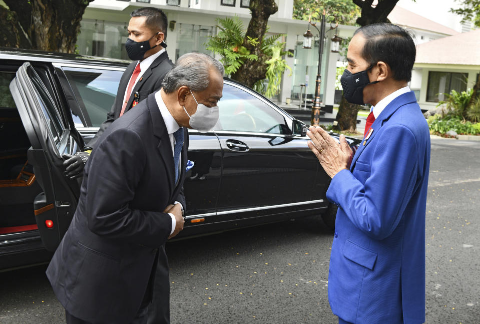 In this photo released by Indonesian Presidential Palace, President Joko Widodo, right, greets Malaysian Prime Minister Muhyiddin Yassin during their meeting at Merdeka Palace in Jakarta, Indonesia, Friday, Feb. 5, 2021. Yassin is currently on a two-day visit in the country. (Agus Suparto, Indonesian President Palace via AP)