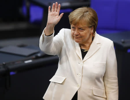 Chancellor Angela Merkel waves during a session of the German lower house of parliament Bundestag to elect a new chancellor, in Berlin, Germany, March 14, 2018. REUTERS/Kai Pfaffenbach