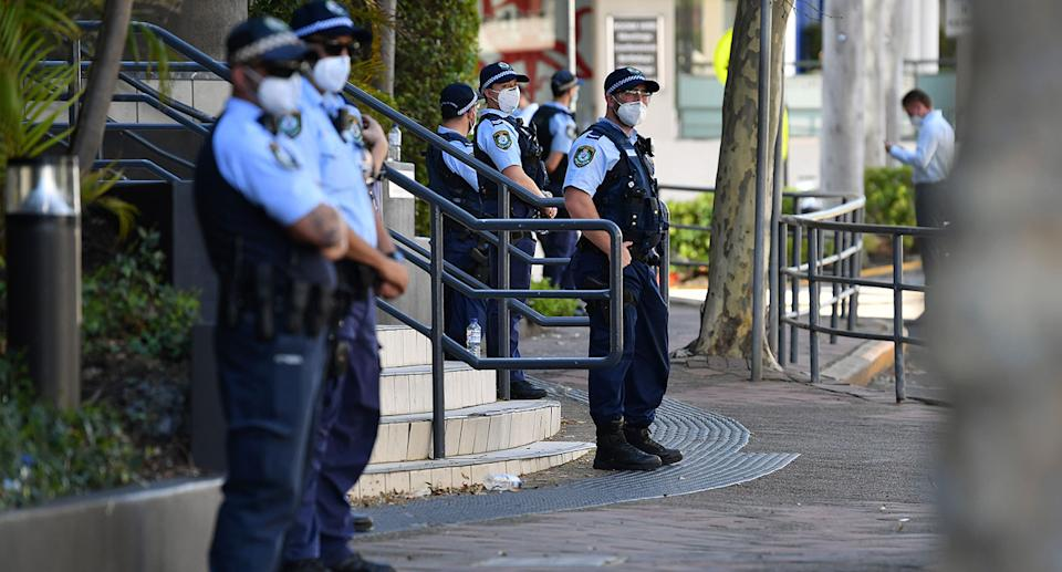 A group of masked officers stand outside a police station in Sydney.