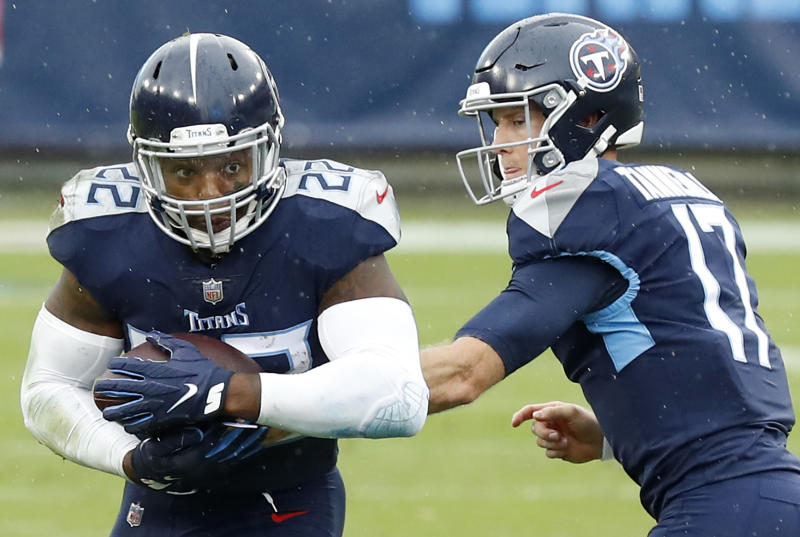Running back Derrick Henry #22 of the Tennessee Titans takes the hand-off from quarterback Ryan Tannehill #17