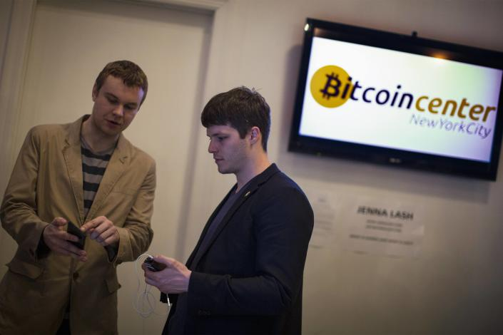 Austin Alexander, deputy director of Bitcoin Center New York City (R) talks about his digital wallet with an attendee during the Satoshi Square at the Bitcoin Center NYC. (Reuters.)
