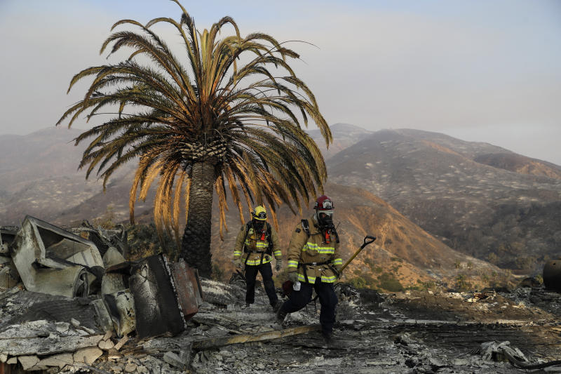 Firefighters Jason Toole, right, and Brent McGill with the Santa Barbara Fire Department walk among the ashes of a wildfire-ravaged home after turning off an open gas line on the property Saturday, Nov. 10, 2018, in Malibu, Calif.  (ASSOCIATED PRESS)