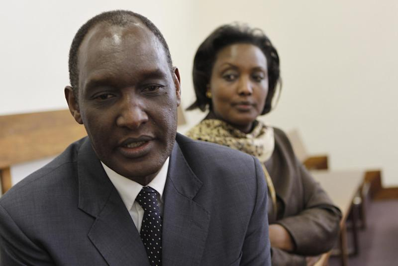 Rwandan exile, Kayumba Nyamwasa, front, and his wife Rosette Kayumba sit in the Johannesburg court Thursday July 12, 2012, after finishing his testimony as a witness in the trial of six East Africans accused of attempted murder in his 2010 shooting. Nyamwasa alleges that Rwandan President Paul Kagame was behind a plot to kill him, and has tried to kill other dissidents around the world. (AP Photo/Denis Farrell)