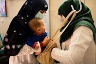 A midwife and a nutrition counsellor weigh a baby at the Tangi Saidan clinic (AFP/Elise BLANCHARD)