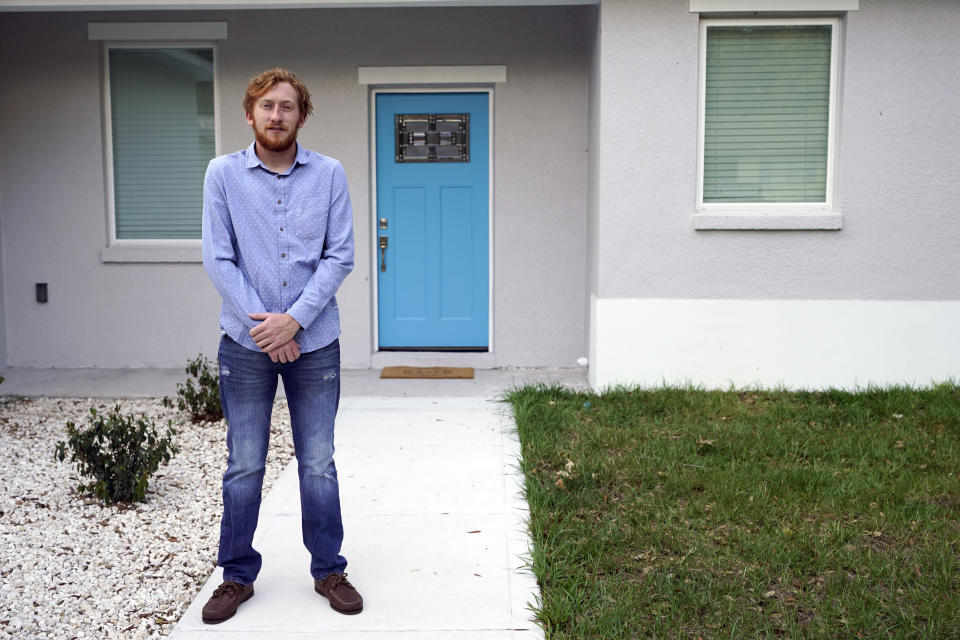 First-time buyer Kevin Muglach stands in front of his new home, Tuesday, April 6, 2021, in Orange City, Fla. Homebuyers are facing the most competitive U.S. housing market in decades this spring, as surging prices and a record-low number of homes for sale narrow the already difficult path to home ownership for many Americans. (AP Photo/John Raoux)