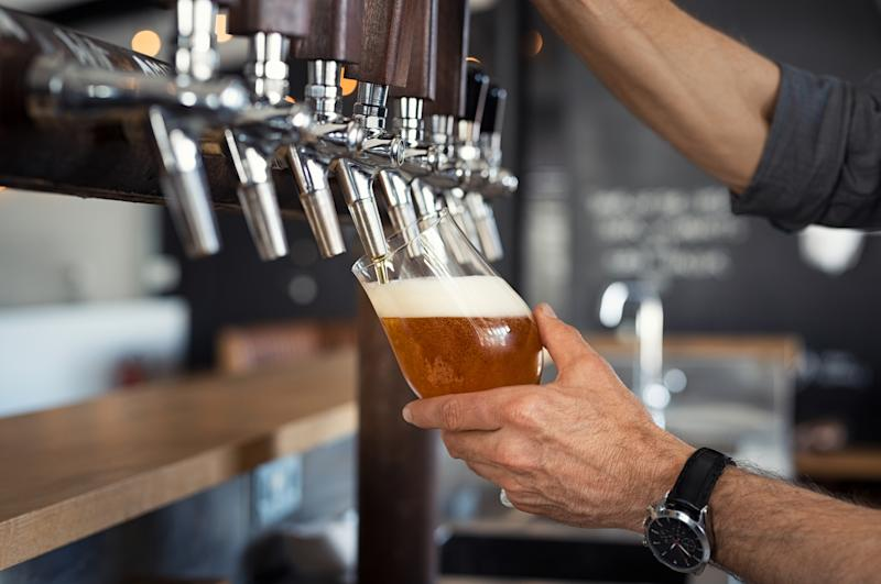 Man pouring draft beer into a glass from a tap