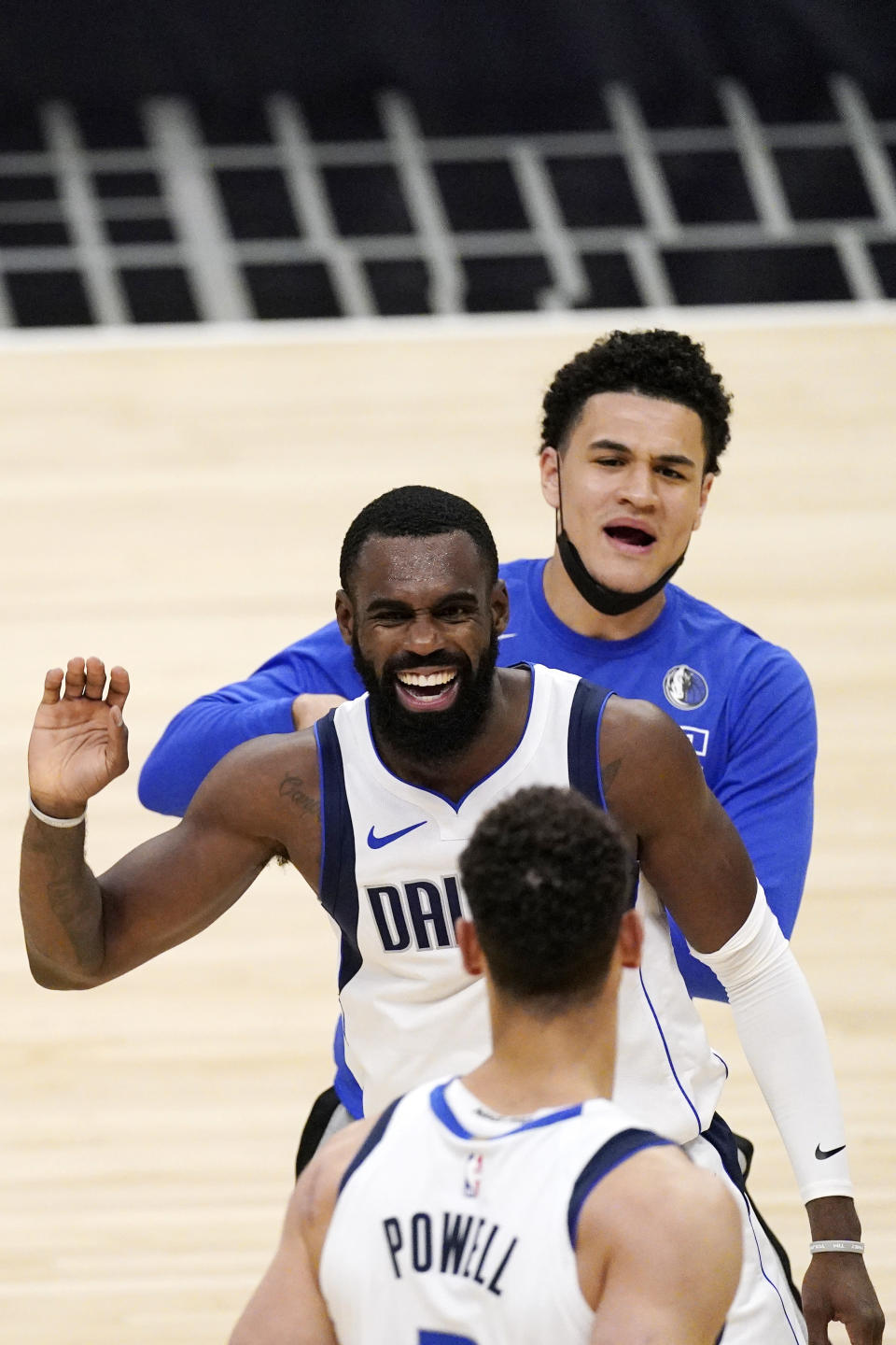 Dallas Mavericks forward Tim Hardaway Jr., center, celebrates with center Dwight Powell, below, and guard Josh Green during the second half in Game 5 of an NBA basketball first-round playoff series against the Los Angeles Clippers Wednesday, June 2, 2021, in Los Angeles. (AP Photo/Mark J. Terrill)